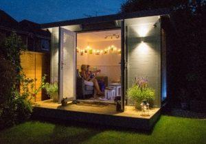 People enjoying a cosy evening in garden room.